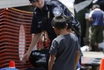 A U.S. Customs and Border Protection officer helps two young boys pick out clothes as they join hundreds of mostly Central American immigrant children as they are being processed.