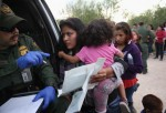 Immigrant Melida Patricio Castro from Honduras shows a birth certificate for her daughter Maria Celeste, 2, to a U.S. Border Patrol agent near the U.S.-Mexico border on July 24, 2014 near Mission, Texas. Tens of thousands of undocumented immigrants, many